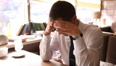 Young man working and bending his head in sadness - stock footage