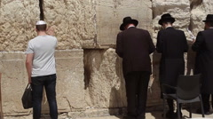 Jews pray and put notes at the Wailing Wall, Jerusalem, Israel - stock footage