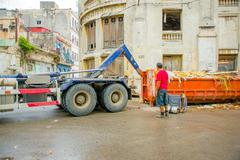 HAVANA, CUBA - DECEMBER 2, 2013: Waste collection vehicle picking up garbage Kuvituskuvat