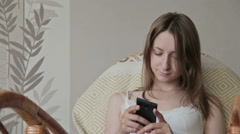 Young beautiful woman sitting with smart phone Stock Footage