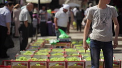 Palestinian boy sells fruit in a busy middle east market, old Jerusalem, Israel Stock Footage