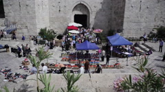 Merchants at Damascus Gate entrance to old Jerusalem, Israel, tilt up - stock footage
