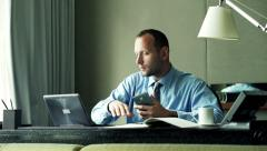 Businessman comparing data on smartphone, laptop and documents sitting in office - stock footage