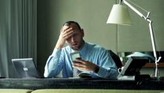 Overwhelmed, unhappy businessman working with smartphone, laptop and documents Stock Footage