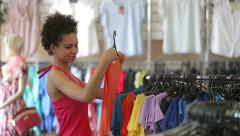 Sale, consumerism: Attractive african american woman chooses clothes in shop - stock footage