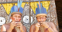 Native Brazilians playing wooden flute at an indigenous tribe in the Amazon Stock Footage