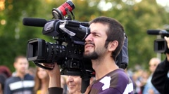 Cameraman shooting concert performance via professional camcorder by a stage Stock Footage