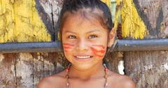 Cute native Brazilian girl smiling at an indigenous tribe in the Amazon - stock footage