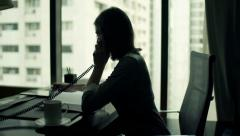 Young businesswoman with documents and tablet talking on phone in office - stock footage