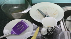 Slow pan, high angle view of dirty dishes piled up in kitchen sink - stock footage
