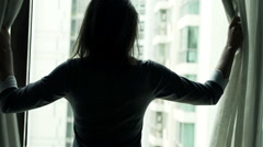 Young businesswoman unveil curtain and looking out of window Stock Footage