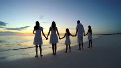 Sunrise silhouette of young Caucasian family enjoying beach lifestyle Stock Footage