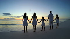 Caucasian family of parents and girls in sunset silhouette on the beach Stock Footage