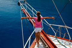 Young girl on the boat with hands in an imaginary flight - stock photo