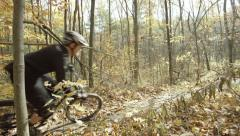 Mountain biker passes frame in slow motion in a colorful fall forest Stock Footage