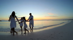 Sunset silhouette of young Caucasian family enjoying beach lifestyle Stock Footage