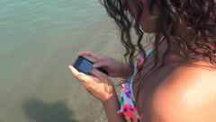 Sunbather girl wearing bikini using a smart phone on summer holidays on the b Arkistovideo