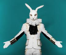 Actor posing in white rabbit suit on color blue background.Studio shot.Halloween - stock photo