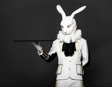 Actor posing in white rabbit suit with tray on black background.Studio shot - stock photo