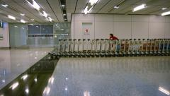 Airport personnel using a motorized, robotic tractor to move luggage carts Stock Footage
