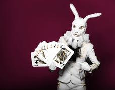 Actor posing in white rabbit suit with playing cards on bright  color red - stock photo