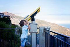 Curious boy, looking through a telescope at something interesting - stock photo