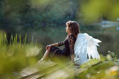 On the pier sits angel girl. - stock photo