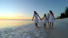 Caucasian family wearing white clothes barefoot on beach at sunset Stock Footage
