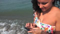 Young girl typing on cellphone on sea beach. Steadycam shot Stock Footage