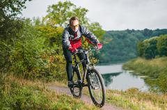 Cyclist riding mountain bike river Stock Photos