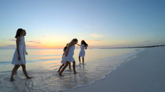 Caucasian family in white clothes barefoot on beach together at sunset Stock Footage