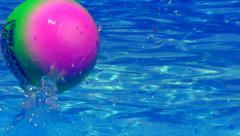 Colorful ball thrown into Swimming Pool - Close up Stock Footage