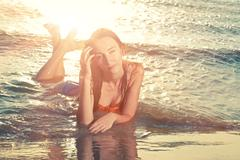 Young girl lying on the beach, sunbathing and relaxing. Summer journey to the Stock Photos