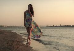 Young woman in a colorful dress on the ocean coast - stock photo