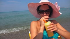 Smiling woman having drink on beach relaxing on chair. Steadycam uhd stock fo Stock Footage
