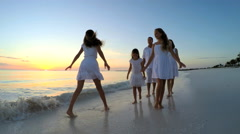 Caucasian family of parents and female children on the beach at sunset - stock footage