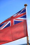 Stock Photo of British maritime red ensign flag blue sky
