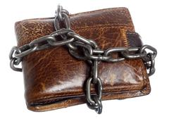 Empty wallet in chain - poor economy, end of spending - stock photo