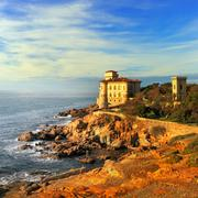 Boccale castle landmark on cliff rock and sea on warm sunset. Tuscany, Italy - stock photo