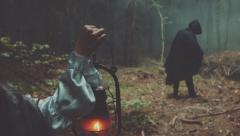 Girl with lantern and among male figure in the terrible forest. Wonderful scene Stock Footage