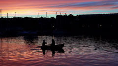 Two people in small row boat at sunset - stock footage