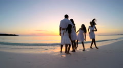 Caucasian family wearing white clothes barefoot on beach at sunset - stock footage