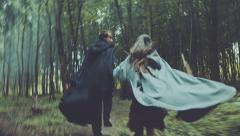 Harassment two unknowns in raincoats, running misty forest Stock Footage