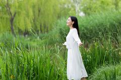 beautiful young girl in the reeds in the summer - stock photo