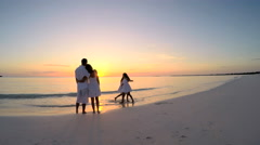 Happy Caucasian family enjoying beach vacation at sunset - stock footage