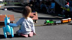 Child watching model train. Exterior location. Stock Footage