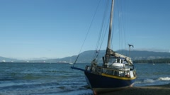 Sailboat washed up on shore on a windy day. Kits Beach Vancouver BC Canada Stock Footage