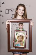 Adult sister holding portrait with her family - stock photo
