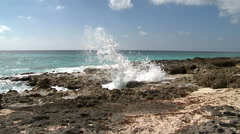Tropical Breakers Splash onto Rocky Caribbean Beach on Sunny Day - stock footage