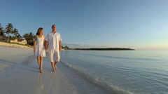 Caucasian couple wearing white clothes barefoot on the beach Stock Footage